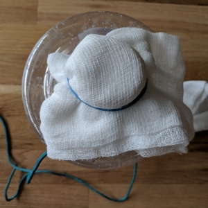 attach the cheese cloth to the water container using the rubber band